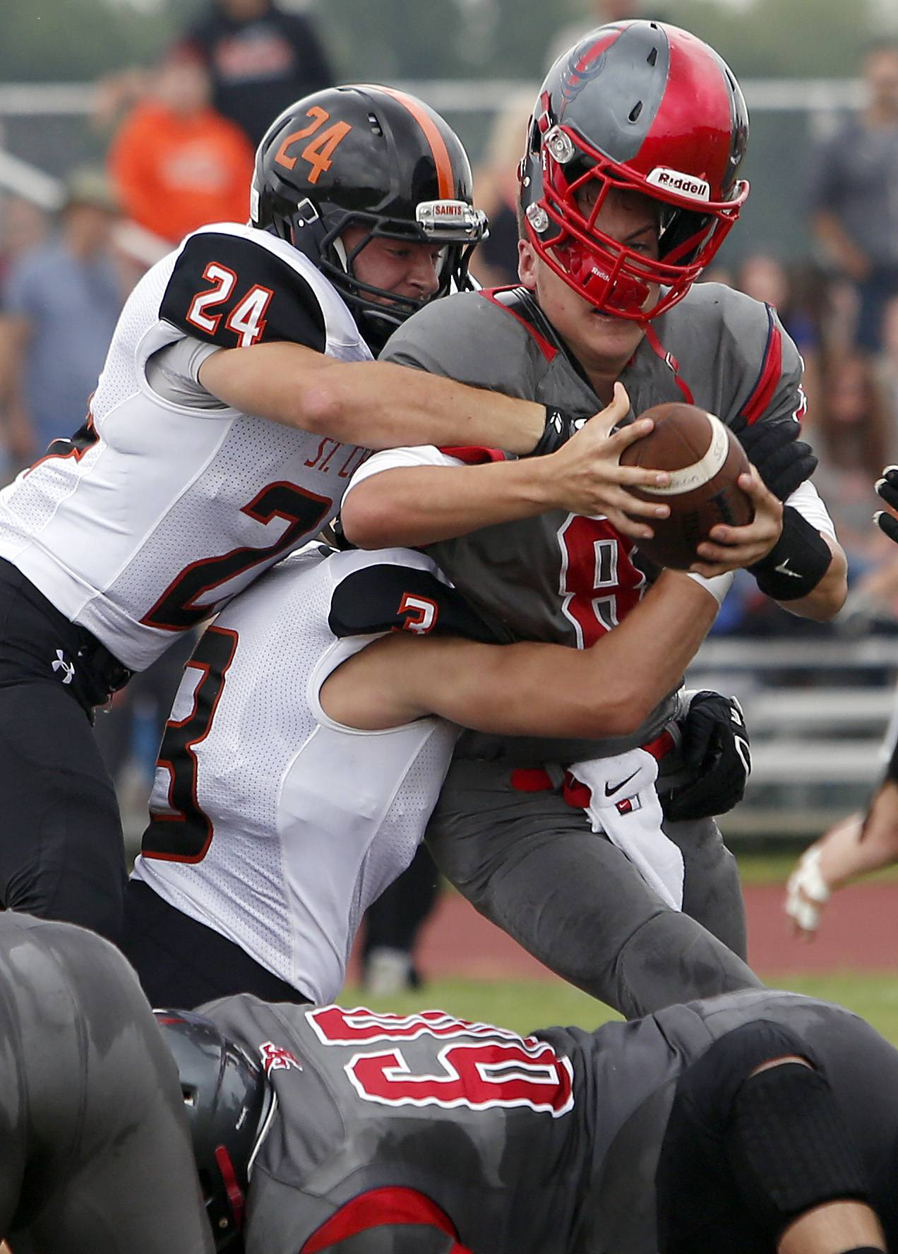 South Elgin quarterback Nate Gomez has his helmet knocked off as he is wrapped up by St. Charles East defensive back Nicholas Sherman (24) and linebacker David McDermott Saturday in South Elgin.