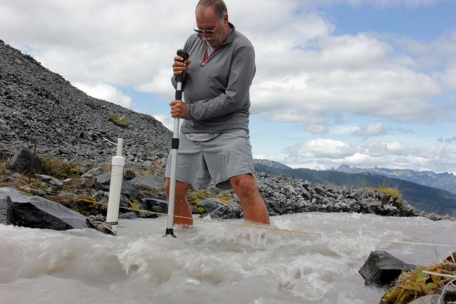 In this Aug. 7, 2015, photo scientist Oliver Grah measures the velocity of a stream of glacier melt stemming from Sholes Glacier in one of Mount Baker's slopes in Mount Baker, Wash. Glaciers on Mount Baker and other mountains in the North Cascades are thinning and retreating.