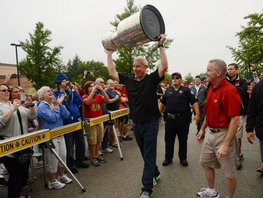 Blackhawks team President and CEO John McDonough hoists the Stanley Cup on Saturday as Elk Grove Village Mayor Craig Johnson leads a short parade to celebrate the team's third NHL championship in six years.