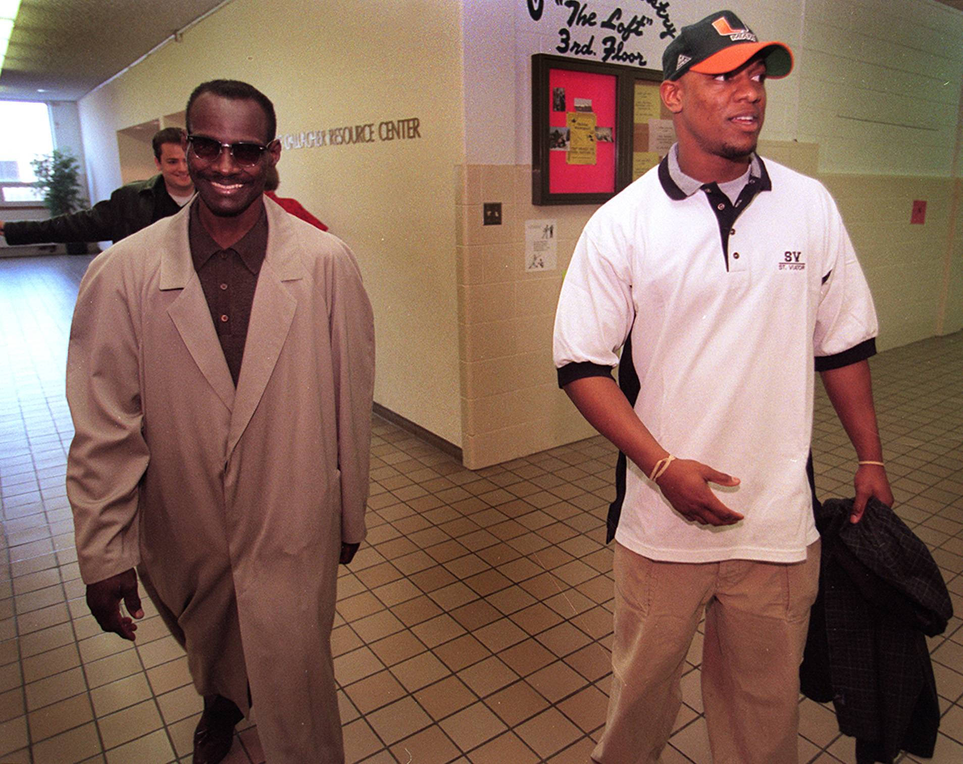 Walter Payton and his son, Jarrett, leave St. Viator High School after a news conference where Jarrett announced his intentions to play college football.