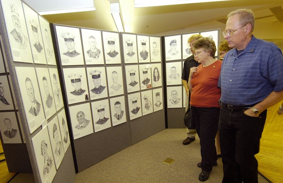 "Gloria and Joseph Caruso of Naperville, parents of Marine Sgt. David M. Caruso, browse through the ""Portrait of a Soldier"" exhibit at the College of DuPage in Glen Ellyn."