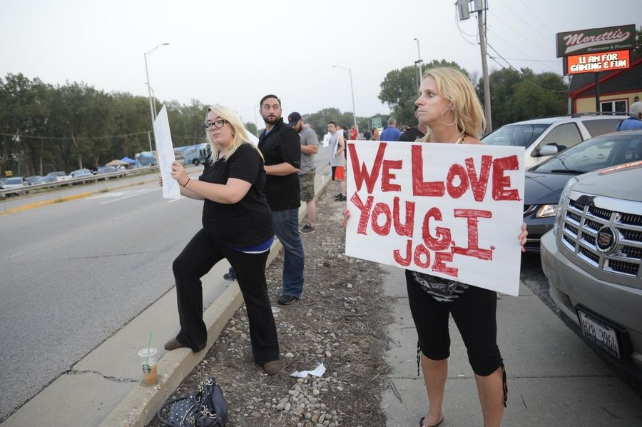 John Starks/jstarks@dailyherald.comRuth Hogan, a Fox Lake business owner, holds a sign with others on Route 12 in Fox Lake Tuesday evening.