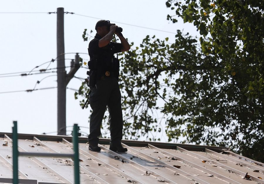 A police officer looks from the roof of a business along Route 59 as police and a SWAT team look for suspects in a shooting death of a Fox Lake police officer Tuesday. A manhunt was conducted in a wetlands area bordering Rollins Road and Route 12.