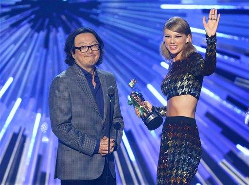 "FILE - In this Aug. 30, 2015 file photo, director Joseph Kahn, left, and Taylor Swift appear on stage as Swift accepts the award for female video of the year for ""Blank Space"" at the MTV Video Music Awards in Los Angeles. Kahn, the director of Swift's new music video is defending the singer after some claimed she whitewashed her video based in Africa. He said in a statement Wednesday, Sept. 2, that the video for ""Wildest Dreams"" includes black people and was produced by a black woman and edited by a black man. (Photo by Matt Sayles/Invision/AP, File)"