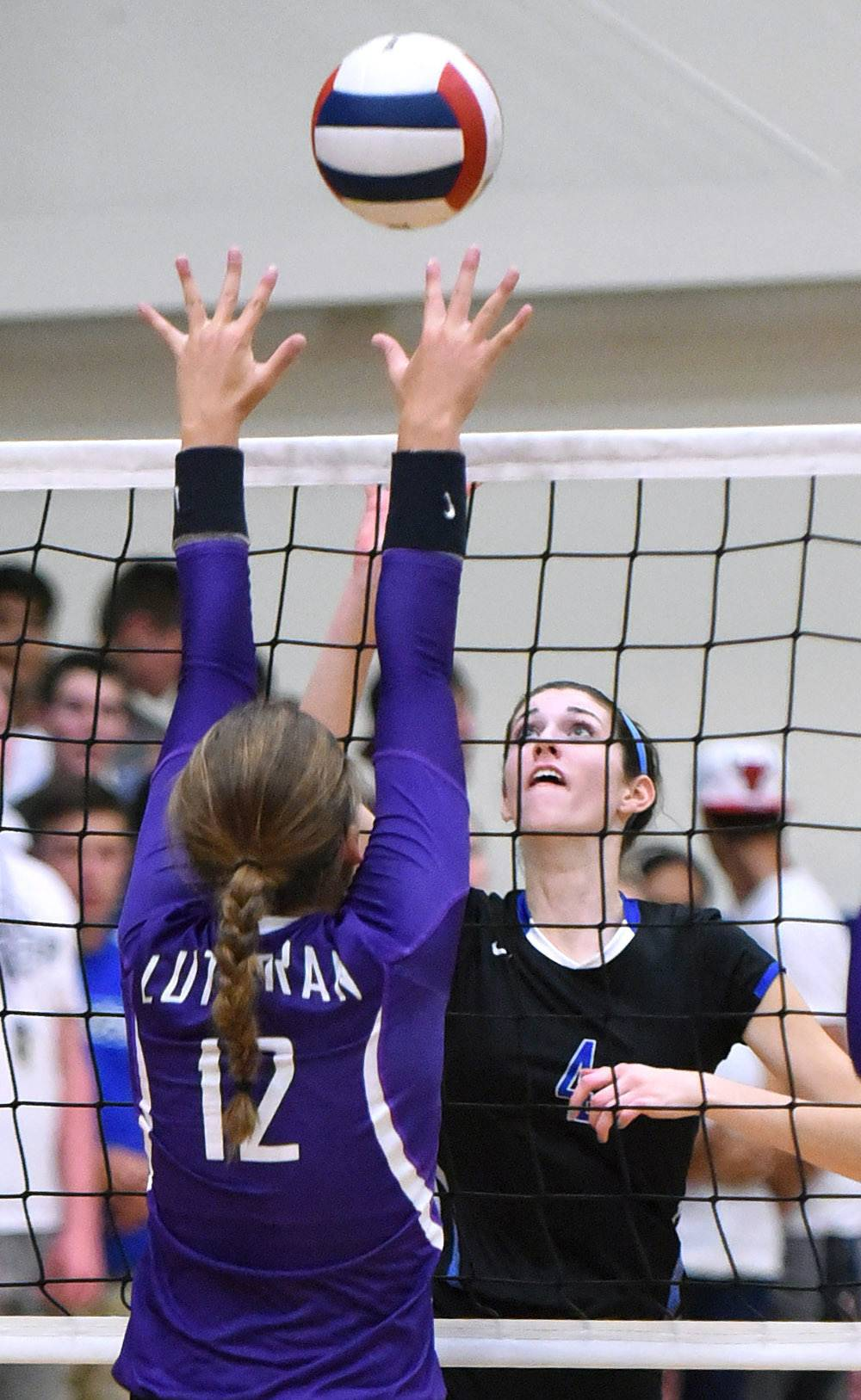 Burlington Central's Madison Hodgson tips the ball over the net to Rockford Lutheran's Mackenzie Zanello Wednesday.