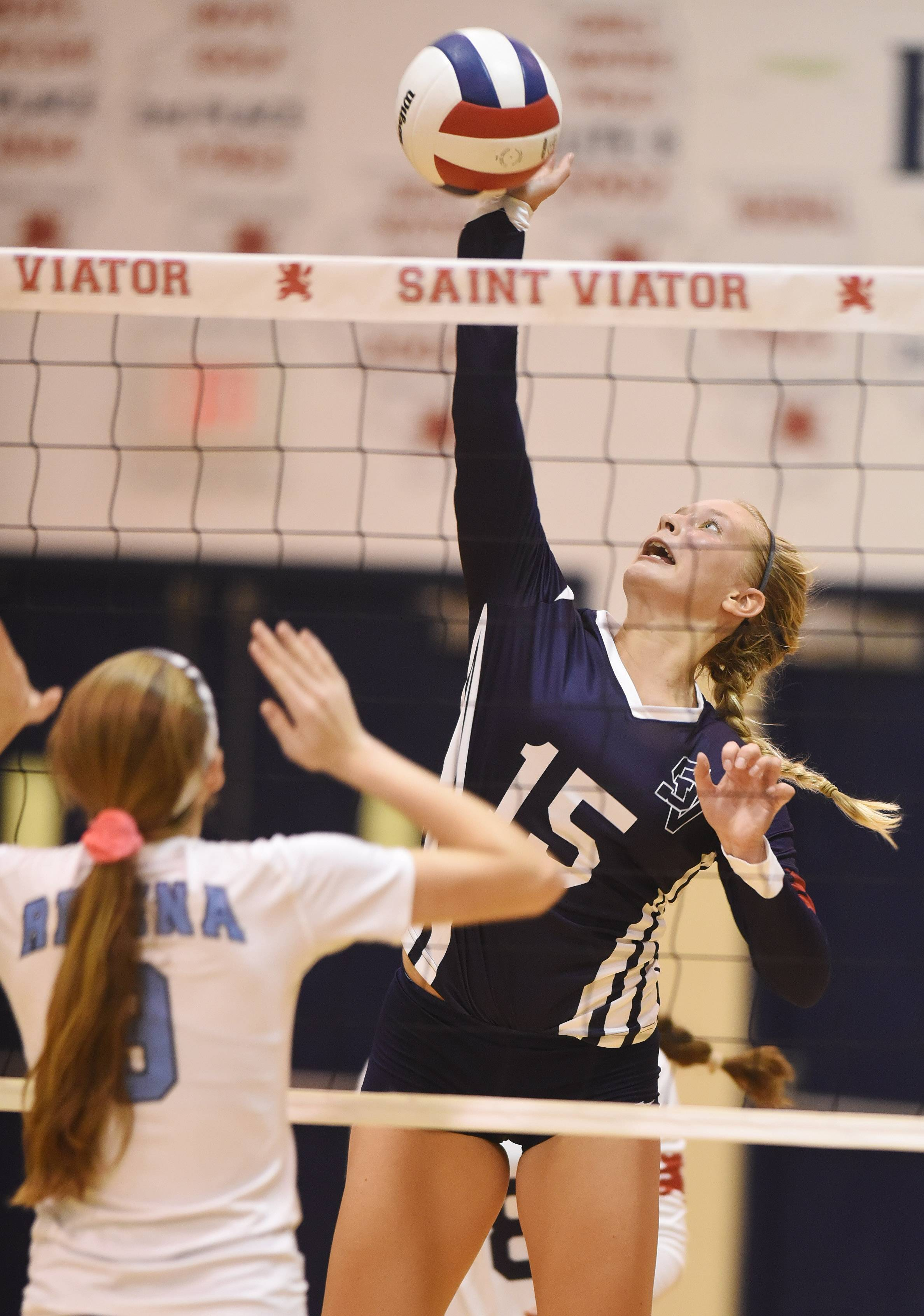 St. Viator's Carrie Leazer, right, leaps for a kill as Regina Dominican's Maddy Fox tries to block the ball at the net during Wednesday's match in Arlington Heights.
