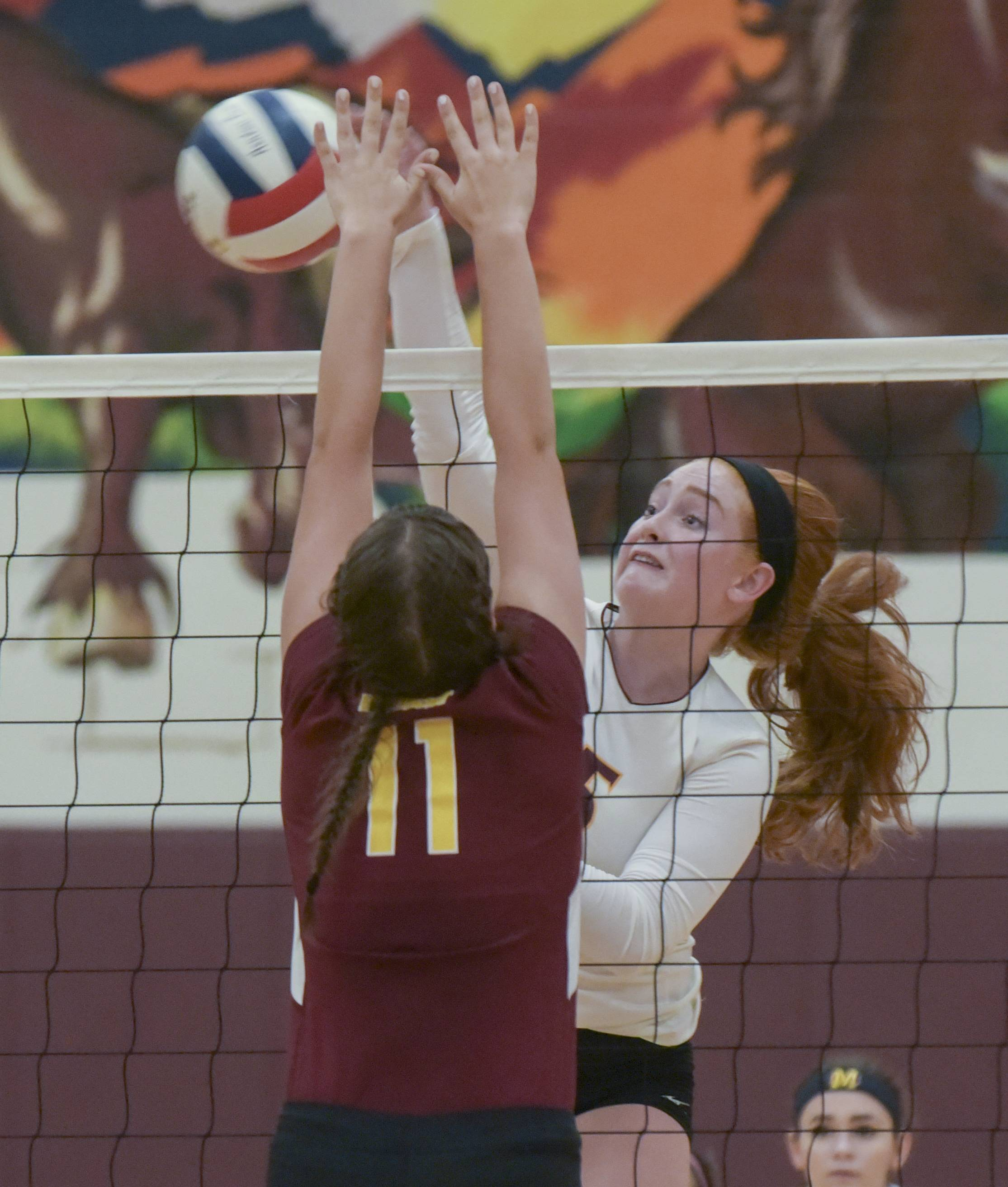 Montini Catholic's Bethany Loftus fires a shot past Westmont's Rachel Chorney during varsity girls volleyball.