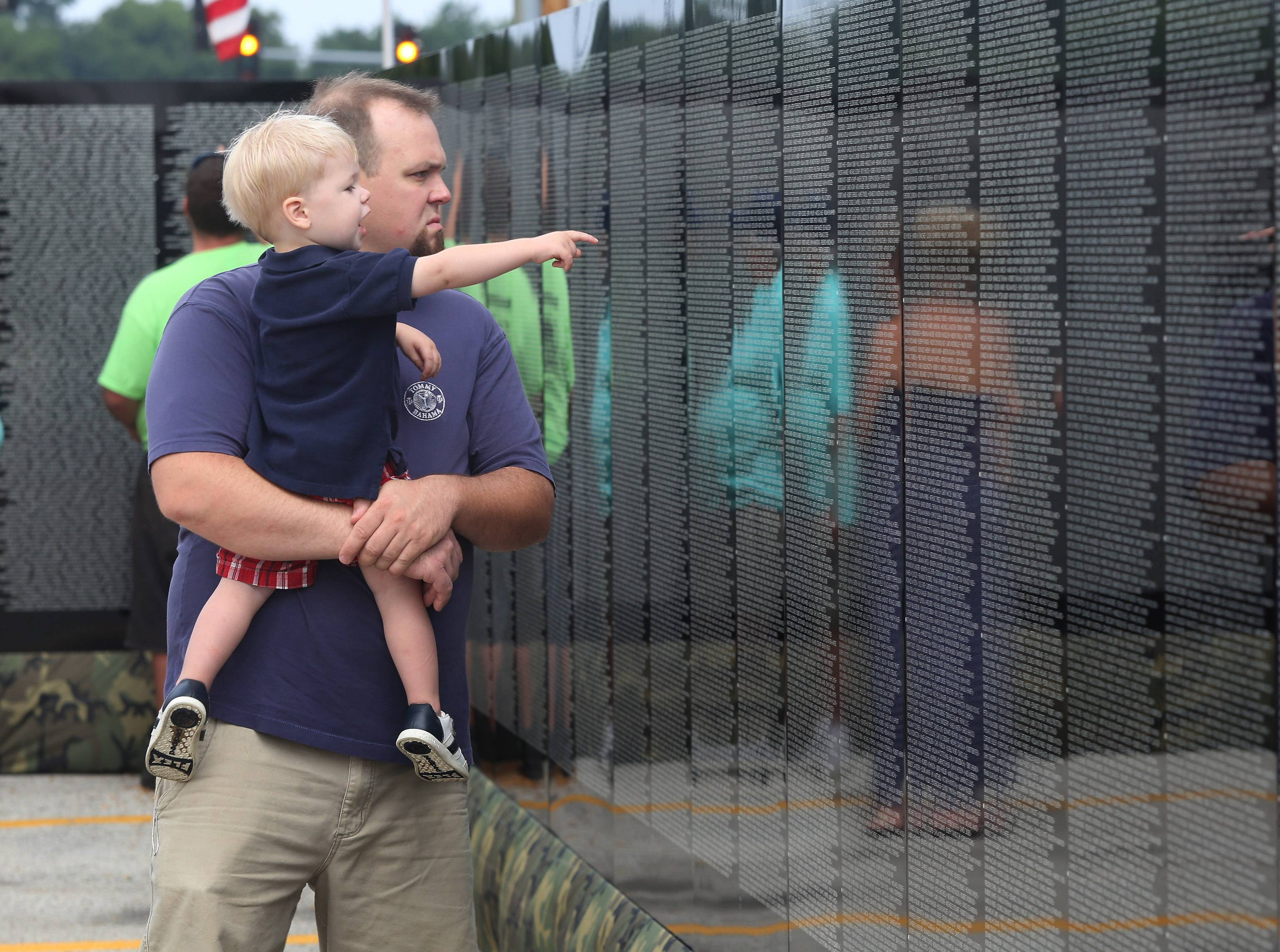 Lee Giernoth and son Andrew, 2, of Lake Villa view the Moving Wall replica Thursday at the parking lot of Home Depot in Round Lake Beach.