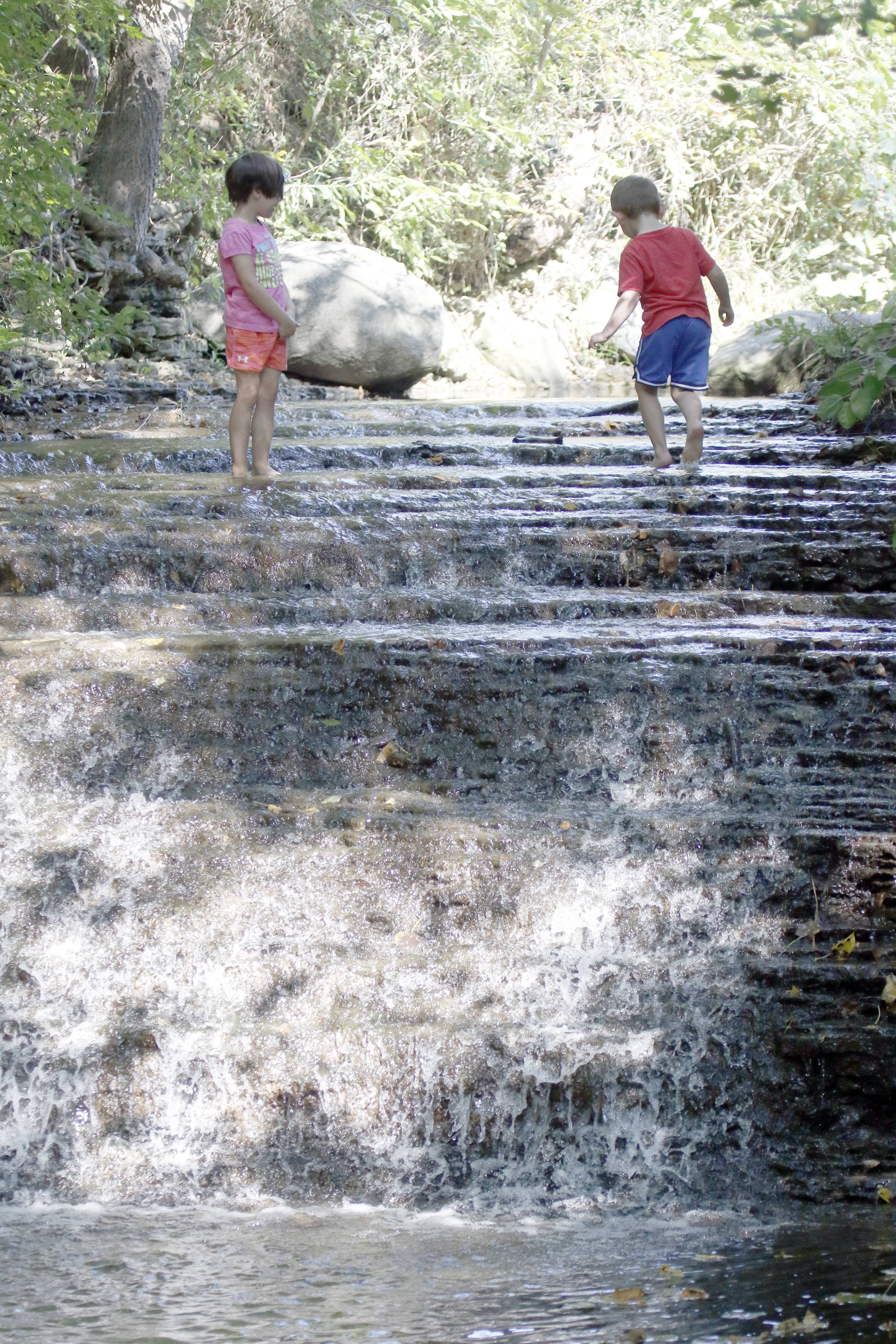 Haddie Hunt and Jacob Kopetsky, both 4 and from West Dundee, walk across the top of a waterfall Thursday at Jon J. Duerr Forest Preserve near South Elgin. To see the waterfall, ride south on the River Bend Bike Trail.