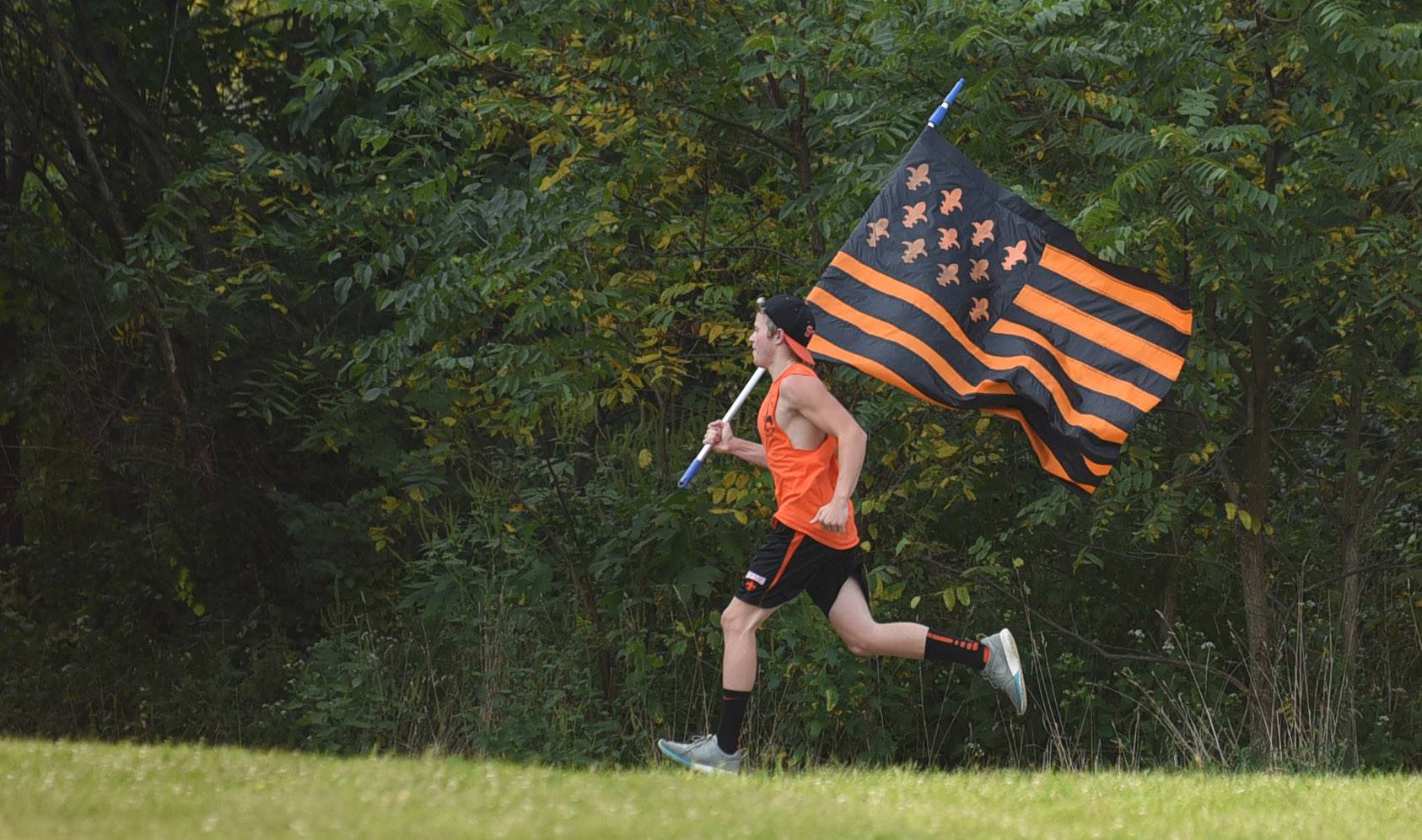 Laura Stoecker/lstoecker@dailyherald.comA St. Charles East Saints cross country fan runs across the route during the Leavey Invitational at LeRoy Oakes Forest Preserve in St. Charles Saturday.