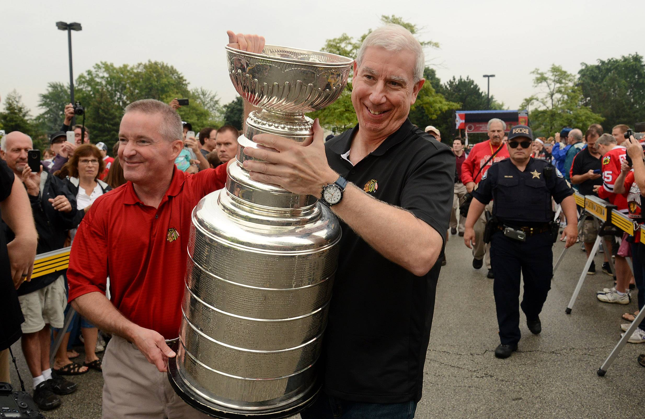 Blackhawks team president and CEO John McDonough and Elk Grove Village Mayor Craig Johnson parade the Stanley Cup at a public rally in Elk Grove Village.