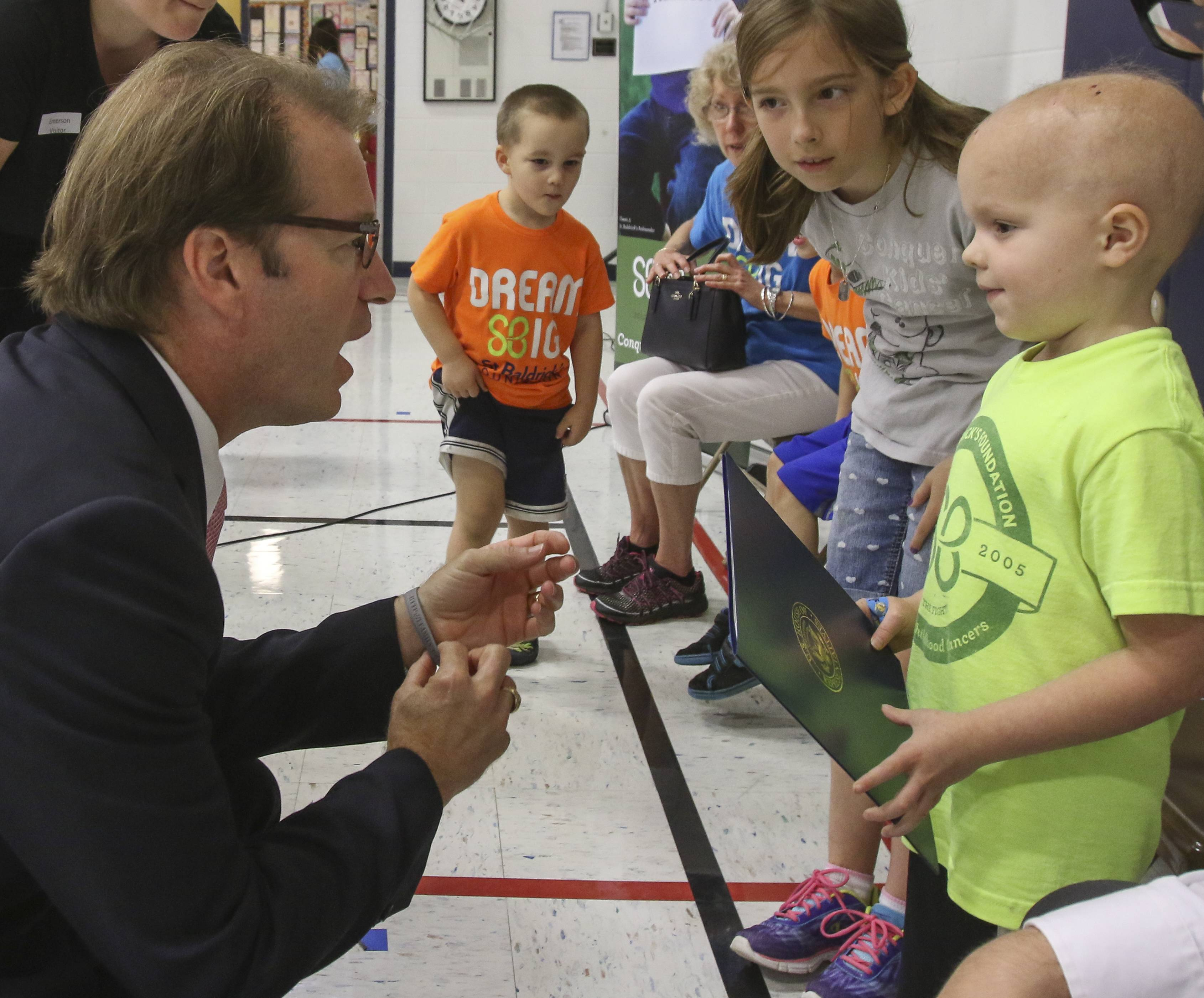 "U.S. Rep. Peter Roskam accepts a ""Chase Away Cancer"" bracelet from 5-year-old cancer survivor Chase Ewoldt at Emerson Elementary School in Wheaton."