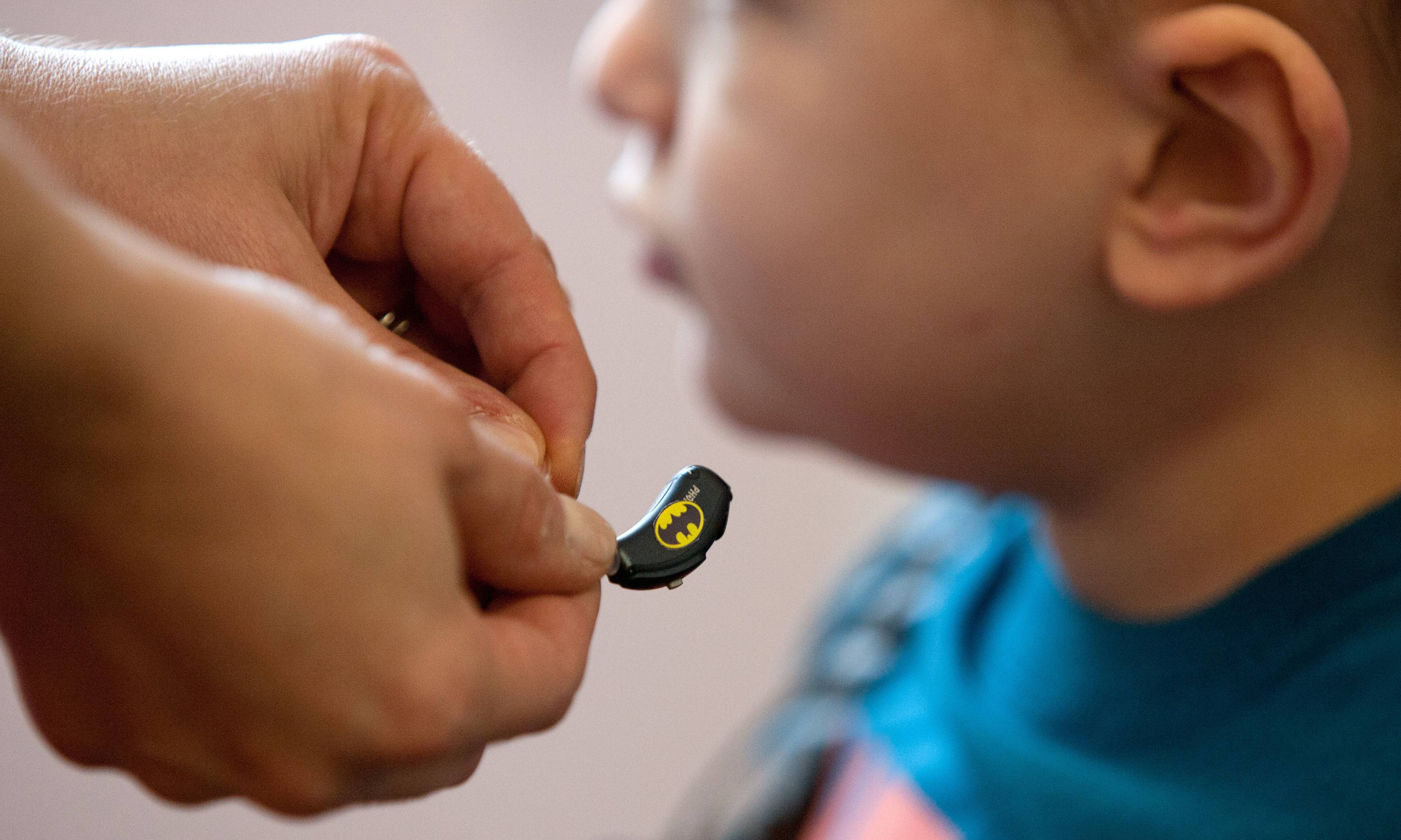 Riley Buckolz, who has several tumors in his brain and spine, receives a hearing aid adorned with the logo of his favorite superhero, Batman, at the Hearing Health Center in Naperville.