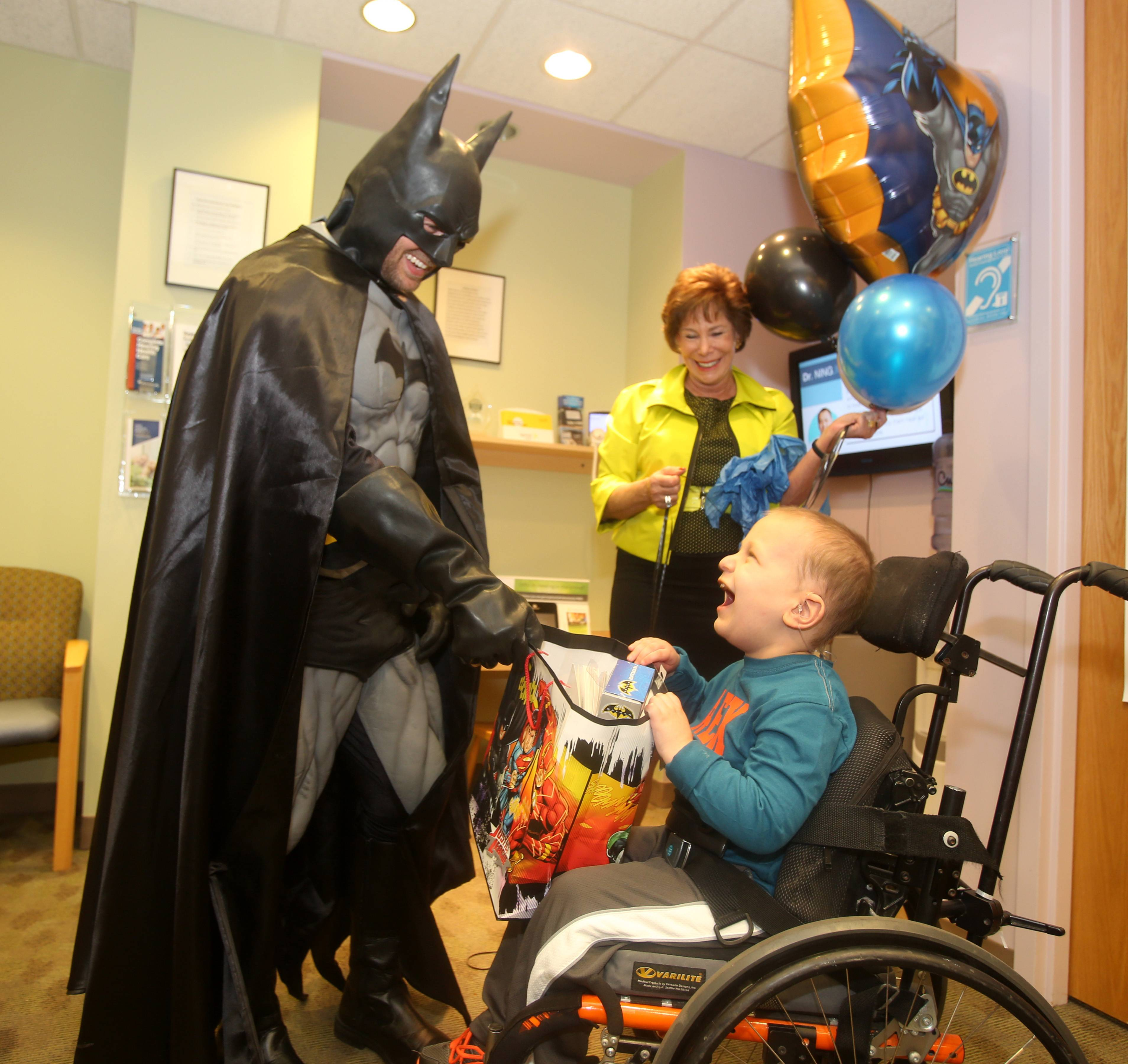 Riley Buckolz, 6, who has several tumors in his brain and spine, not only received free hearing aids at the Hearing Health Center in Naperville, but also got a visit from his favorite superhero, Batman. Dr. Ronna Fisher holds balloons for the occasion.
