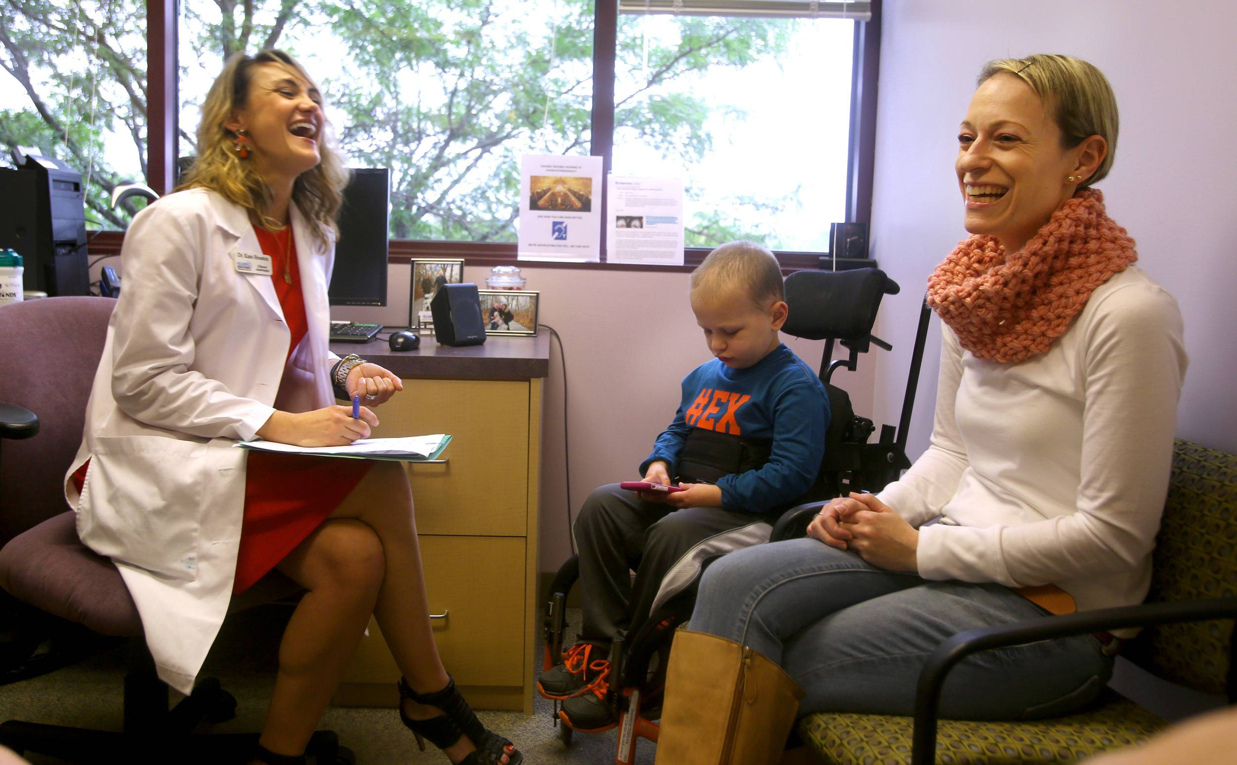 Dr. Kara Houston meets with 6-year-old patient Riley Buckolz and Riley's mom, Adena Buckolz, at the Hearing Health Center in Naperville, where Riley got a visit from his favorite superhero and hearing aids decorated with Batman's logo.