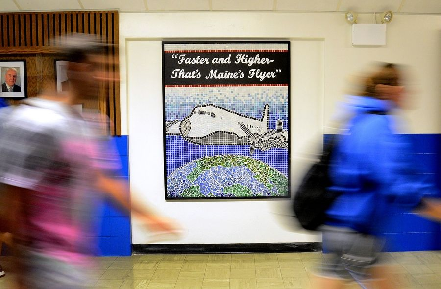 Maine East students shuffle past a mosaic honoring the story of the Maine Flyer, a World War II aircraft dedicated to Maine students who sold $551,000 in war bonds.