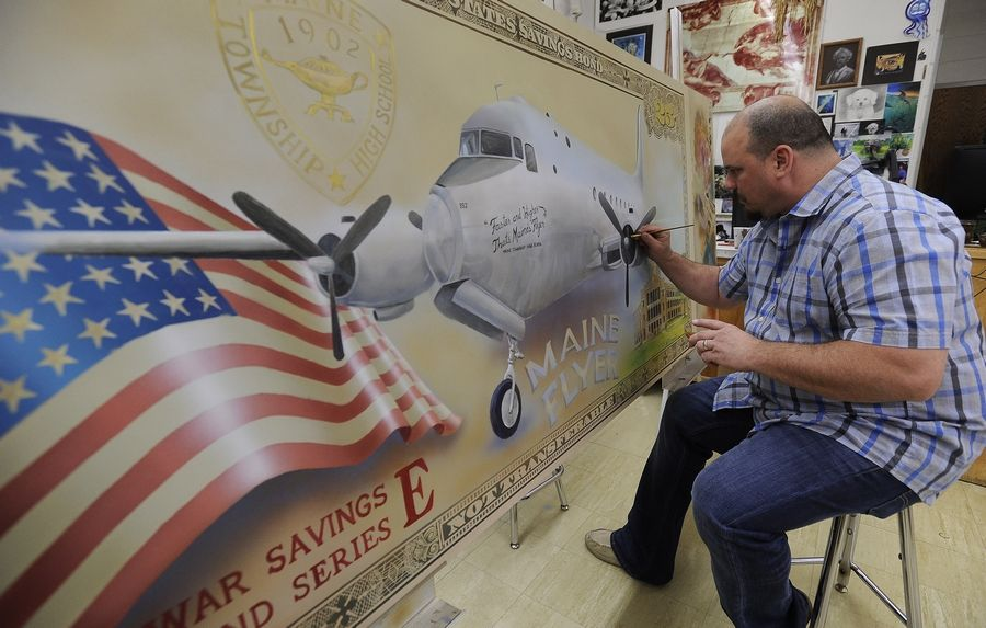 Richard Cammarata, an art teacher at Maine West High School in Des Plaines, puts finishing touches on an acrylic painting of the Maine Flyer, which was dedicated to students who raised money for the war effort 70 years ago.