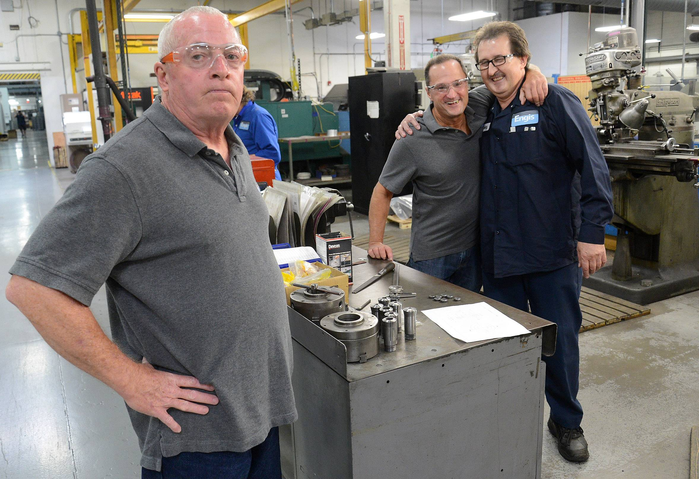 Engis Corp. employees Doug Jones, left, and Greg Nania, center, reunite with Henry Kosinski on his first day back at work Tuesday in Wheeling.