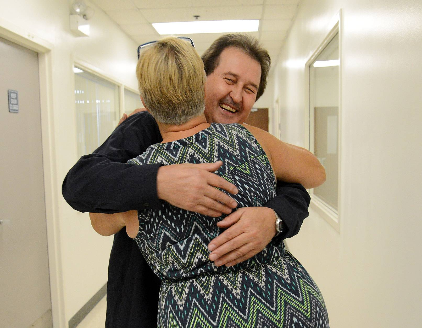 Engis Corp. employee Henry Kosinski is hugged by Customer Service Supervisor Sally Jones on his first day back at work.
