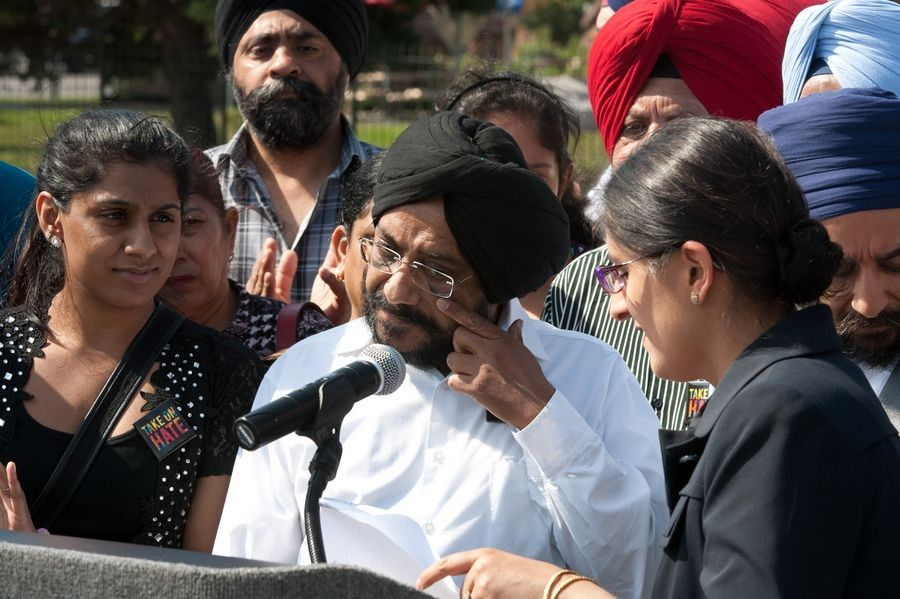 Inderjit Singh Mukker, center, a Sikh-American who was attacked last week, speaks during a Tuesday rally along Cass Avenue in Darien.