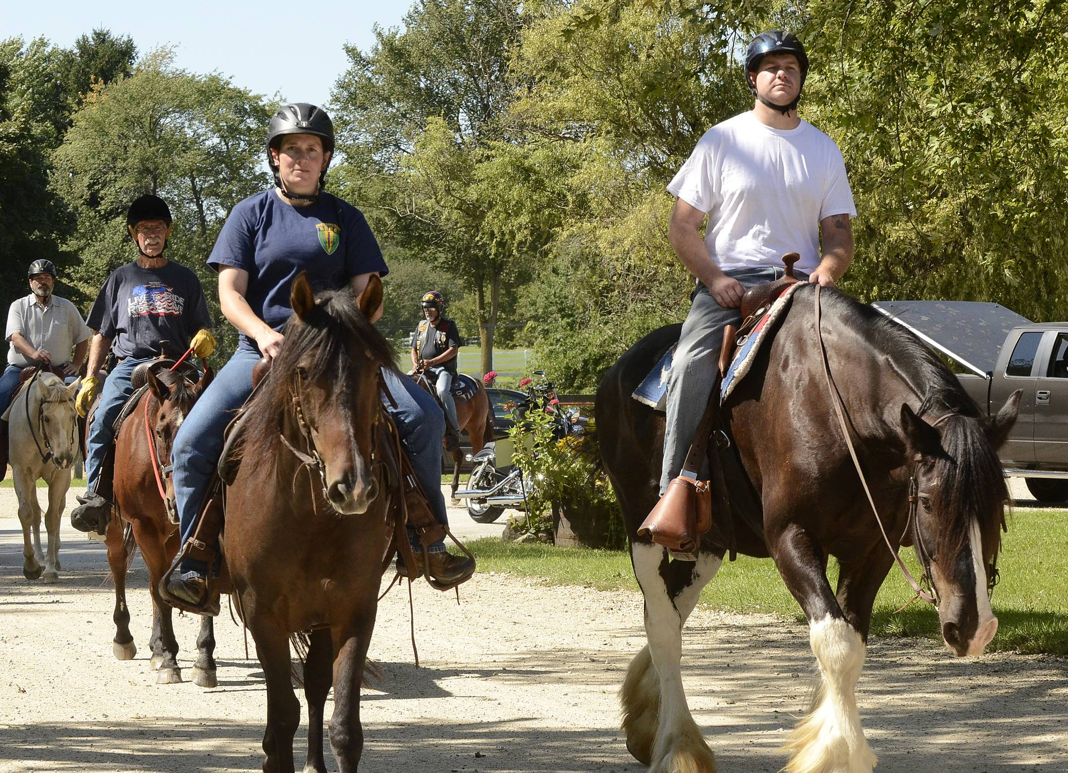 "Mitchell Hedlund of Poplar Grove, an Army veteran of the war in Afghanistan, right, rides out on a trail Monday as about 45 military vets take part in an equine therapy event at the Barrington Hills Riding Center in Barrington Hills. ""This is my cure,"" Hedlund said."