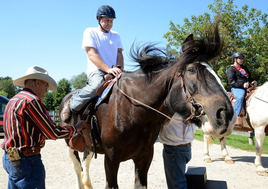 Mitchell Hedlund of Poplar Grove, an Army veteran of the war in Afghanistan, right, prepares to ride out on a trail as part of an equine therapy event at the Barrington Hills Riding Center in Barrington Hills Monday.