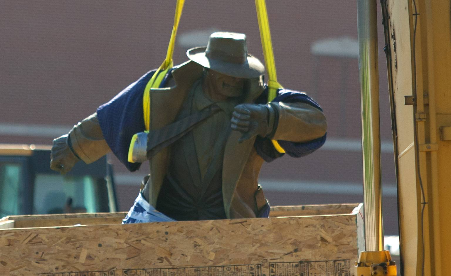 Dick Tracy is lifted Thursday from his perch along the Riverwalk in downtown Naperville. He was taken to temporary storage while a new plaza for the cartoon character sculpture is built at the Water Street District.