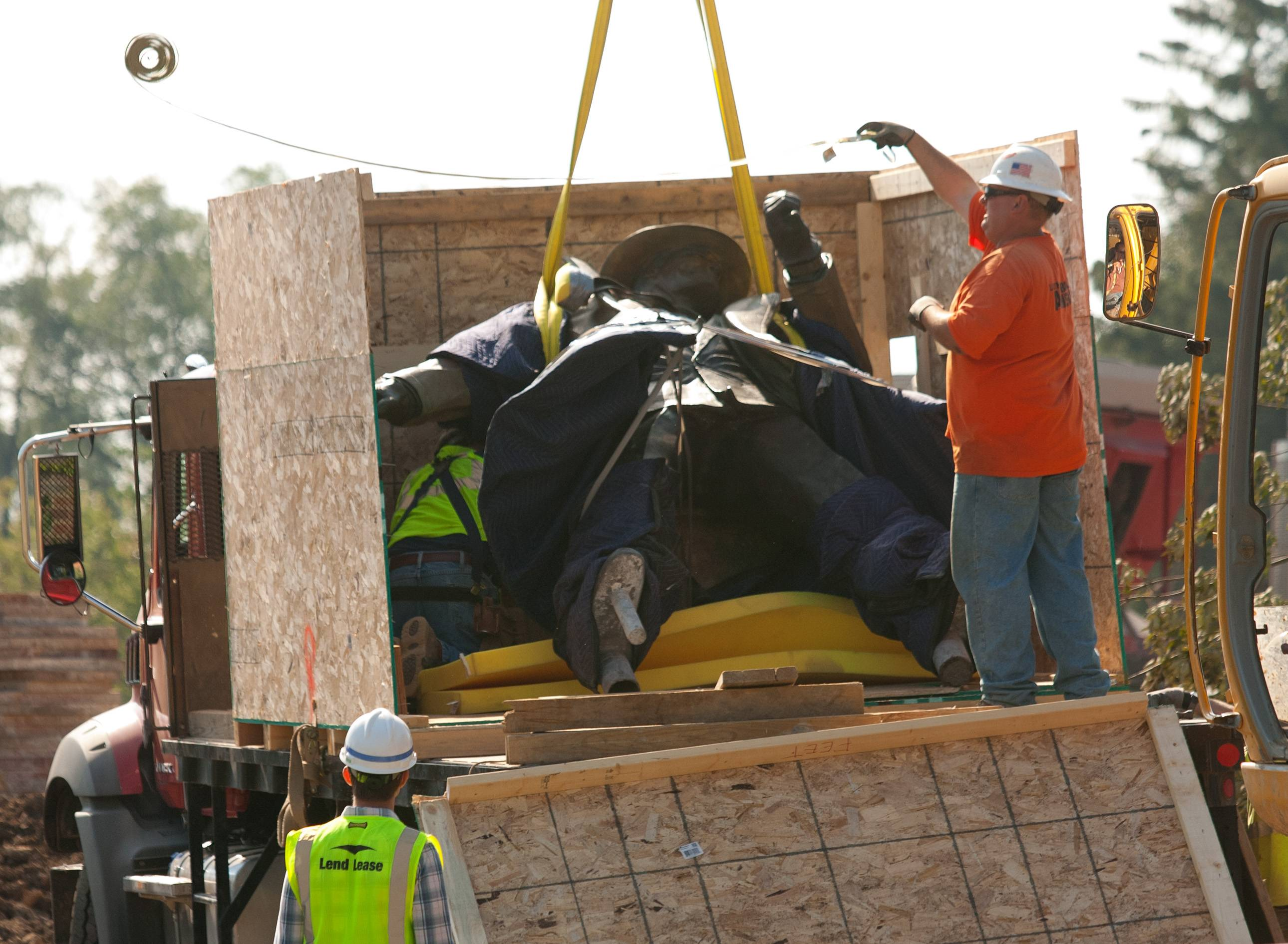 Crews secure the 9-foot-tall sculpture of cartoon detective Dick Tracy on Thursday as they work to move it to temporary storage while a new home for the piece is built as part of the Water Street District project in downtown Naperville.