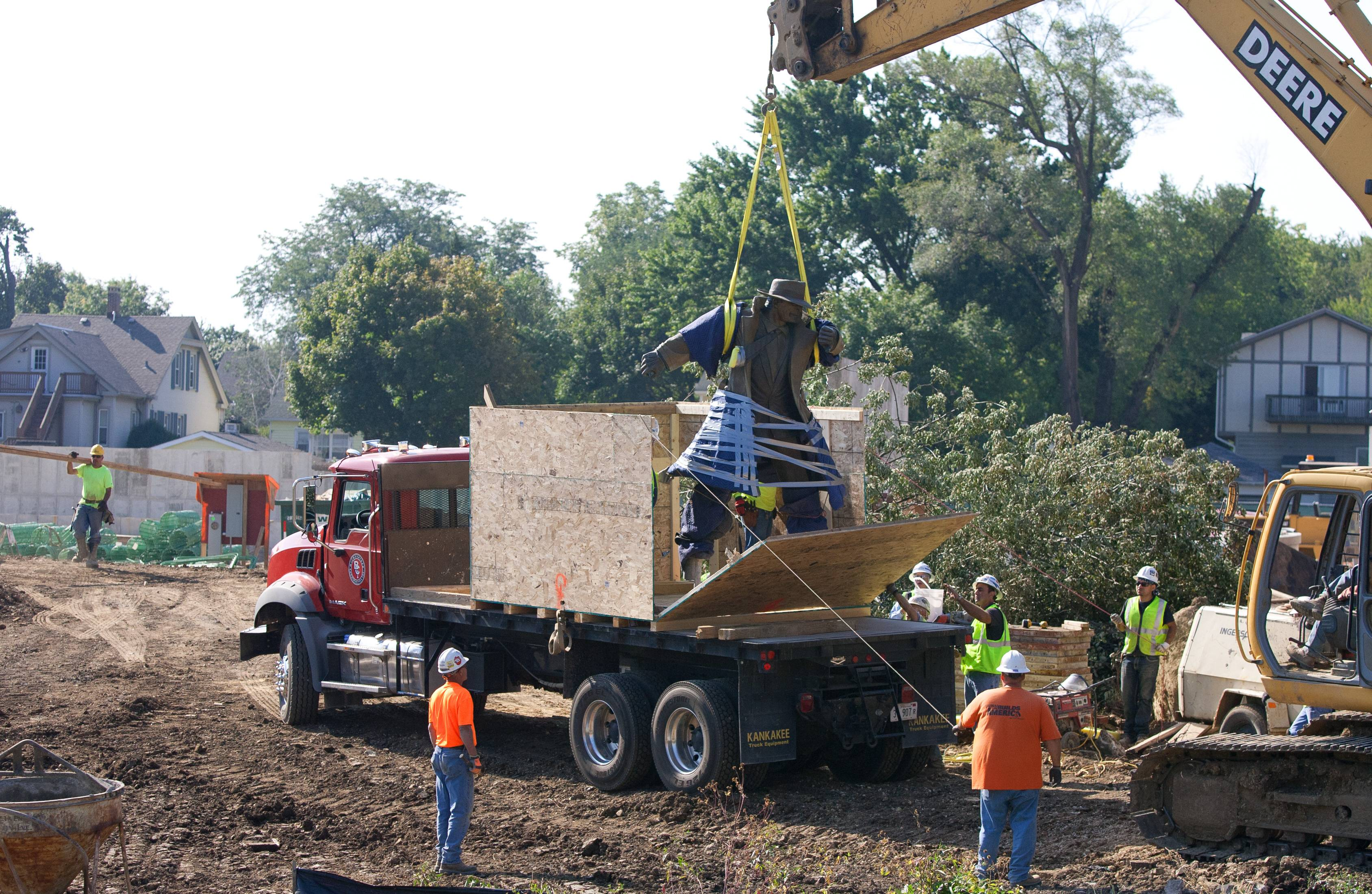 It took a crane to lift the sculpture of cartoon detective Dick Tracy from its base along the Naperville Riverwalk on Thursday. The sculpture is expected to be in storage for about 60 days while a new plaza is built to house it at the Water Street District.