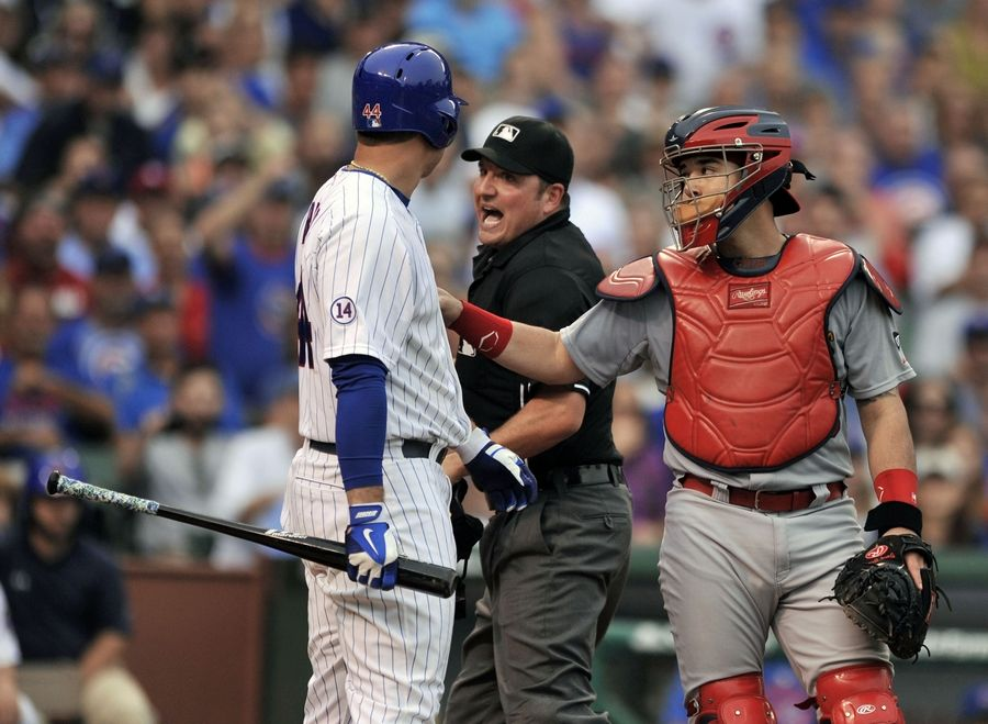 "Anthony Rizzo argues with home plate umpire Dan Bellino after being hit by a pitch while St. Louis Cardinals catcher Tony Cruz holds Rizzo back from charging the mound during the seventh inning on Friday at Wrigley Field. Cubs manager Joe Maddon was irate over Rizzo being hit ""I don't know who put out the hit. I don't if Tony Soprano was in the dugout today. I didn't see him in there. We're not going to put up with that."""
