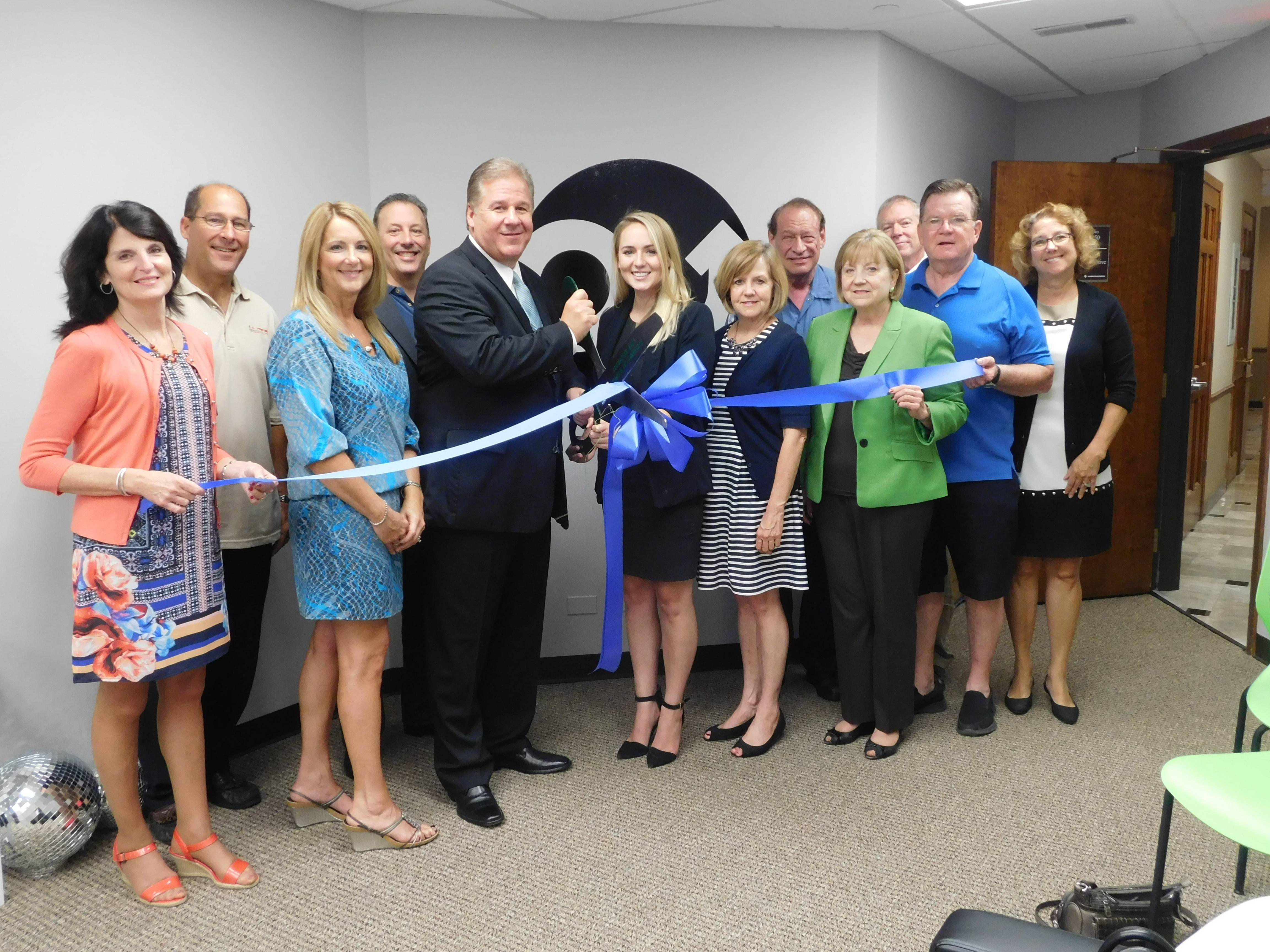 John and Jessie O'Brien, center, cut the ribbon on their OneUp Automotive Inc. business in Barrington.