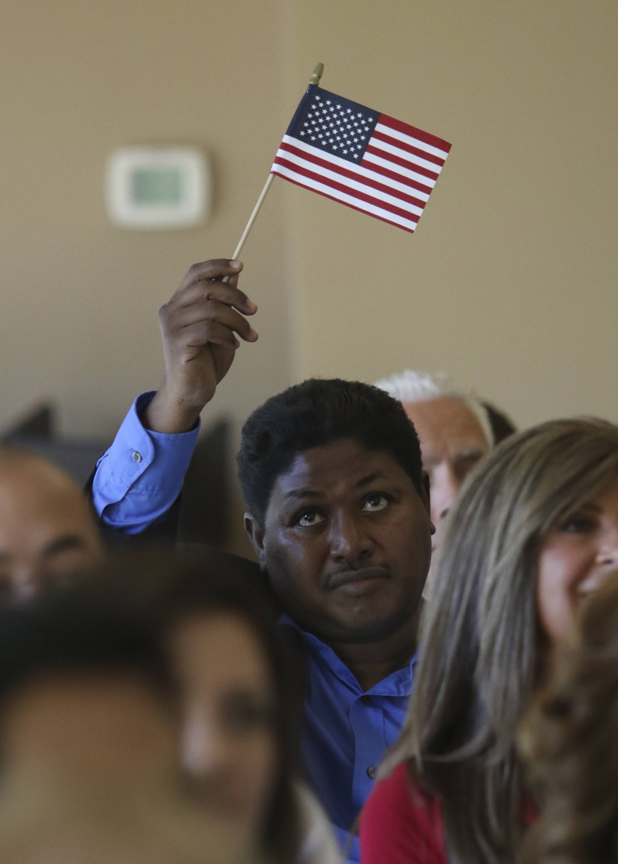 Mohammed Elfaki, who is originally from Sudan, waves the American flag as he becomes a U.S. citizen during the naturalization ceremony for new citizens at Cantigny Park in Wheaton on Thursday.