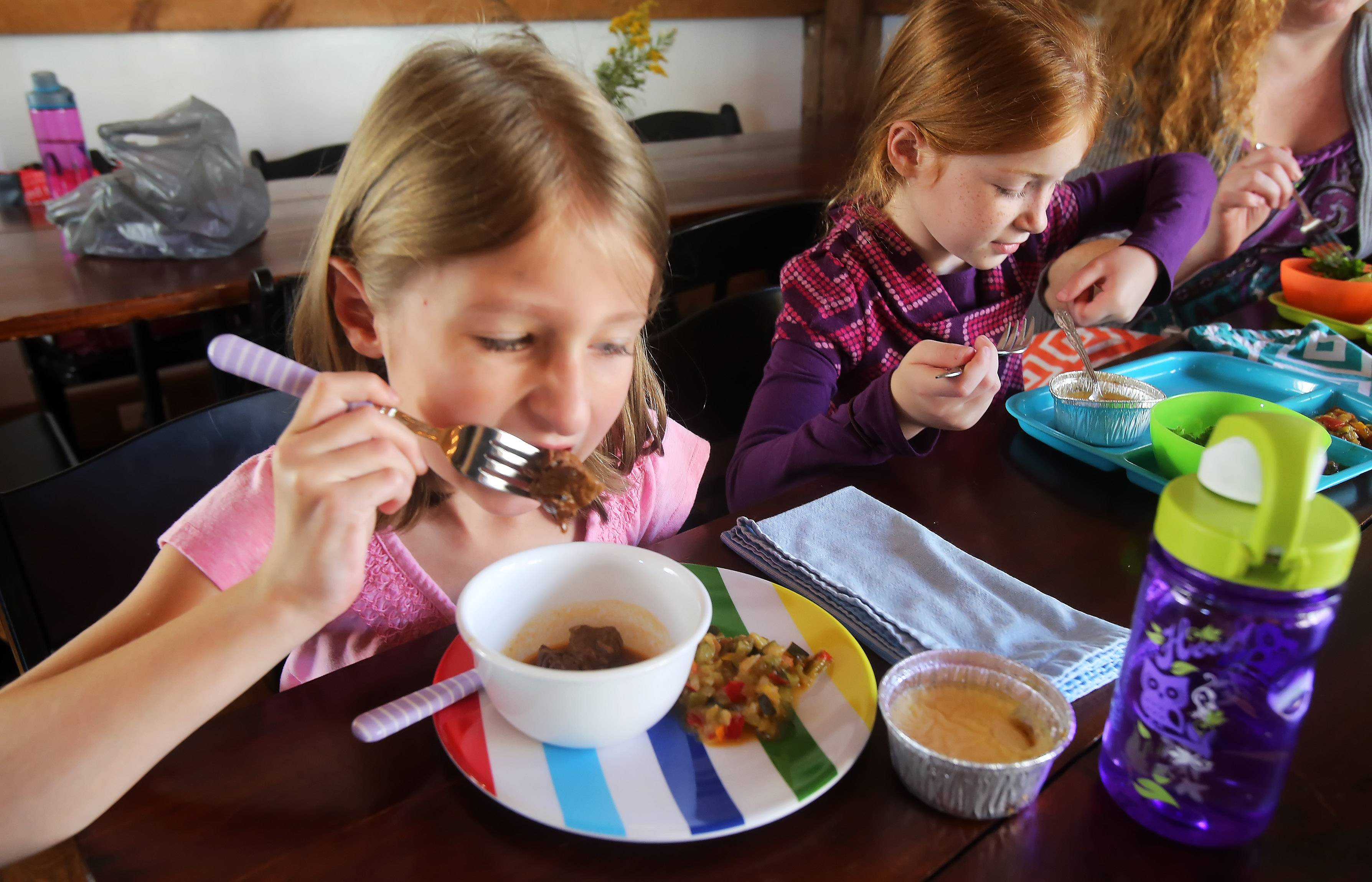 Second graders Grace Muschlitz, left, and Gwyn Johnson eat beef bourguignon and crème caramel for lunch made by Chef Jean-Marc Loustaunau at Prairie Crossing Charter School in Grayslake on Wednesday. The Cafe Pyrenees chef created the meal as part of the school's Farm to Table.