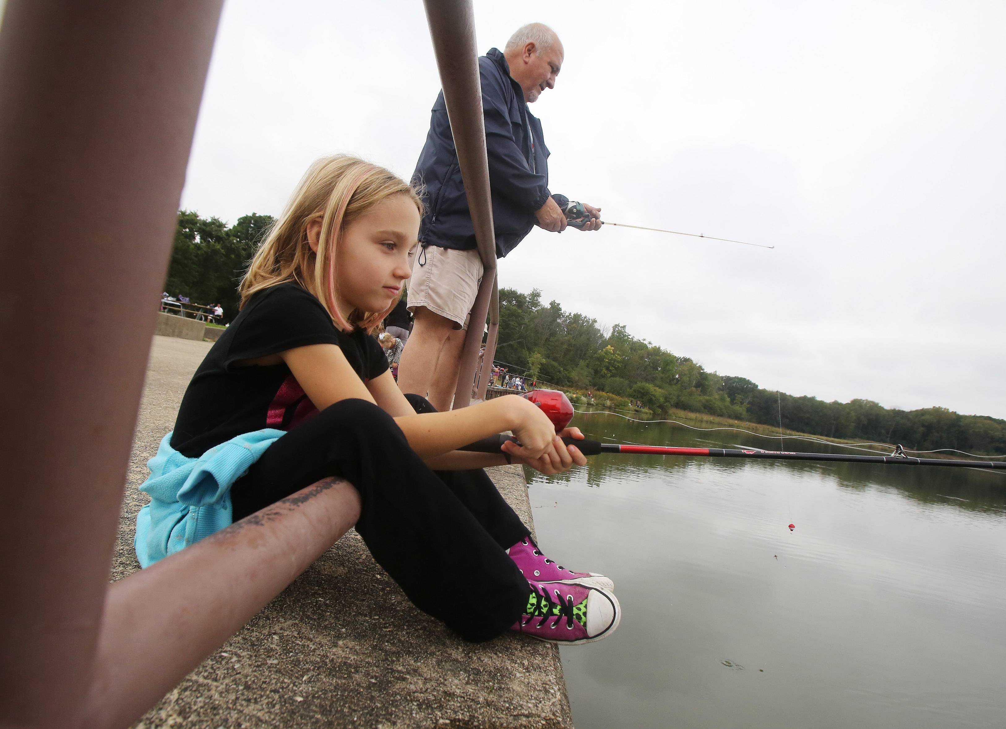 Gilbert R. Boucher II/gboucher@dailyherald.comLilli Kersting, 8, of Hoffman Estates fishes with her grandfather, Jim Rambert, during the annual fishing derby hosted by Cook County Commissioner Timothy O. Schneider at Busse Woods Forest Preserve in Elk Grove Village on Sunday. The event was part of 100 events in one week to celebrate the 100th anniversary of the Cook County Forest Preserves.