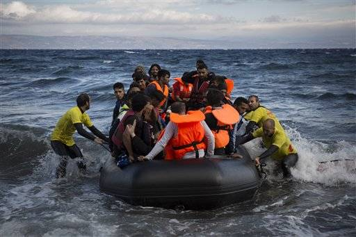 Four lifeguards from Barcelona, Spain, working as volunteers, help disembarking a dinghy as migrants and refugees arrive from the Turkish coasts to the northeastern Greek island of Lesbos, on Wednesday, Sept. 30, 2015. The International Organization for Migration says a record number of people have crossed the Mediterranean into Europe this year, now topping a half a million, with some 388,000 entering via Greece.