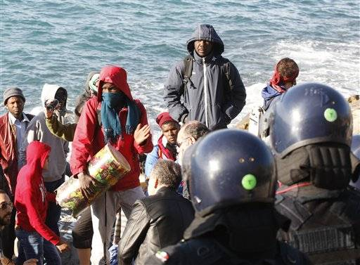 Refugees and migrants face Italian police officers in riot gear at the Franco-Italian border in Ventimiglia, Italy, Wednesday, Sept. 30, 2015. Italian police have emptied out a migrant tent camp in the border city of Ventimiglia, prompting dozens of migrants to flee to rocks along the shoreline.