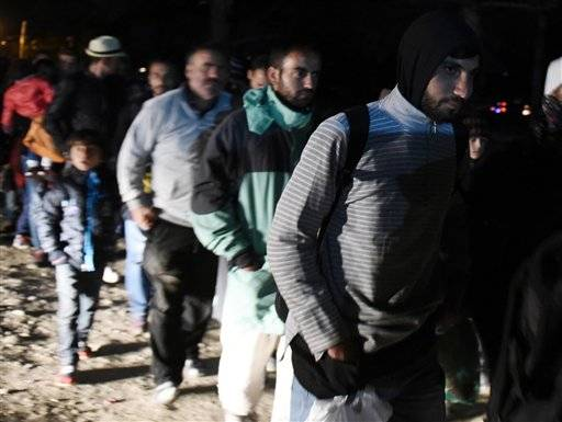 Syrian Hussam Jaban, foreground, walks to cross the border from the northern Greek village of Idomeni into Macedonia, on Wednesday, Sept. 30, 2015. Jaban, 21, said he swam to a small Greek island from the nearby Turkish coast to avoid paying smugglers for the crossing. The International Organization for Migration says a record number of people have crossed the Mediterranean into Europe this year, now topping a half a million.