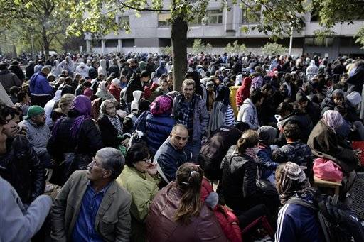 Hundreds of migrants and refugees wait for their registration at Berlin's central registration center for refugees and asylum seekers LaGeSo (Landesamt fuer Gesundheit und Soziales - State Office for Health and Social Affairs) in Berlin, Germany, Wednesday, Sept. 30, 2015.