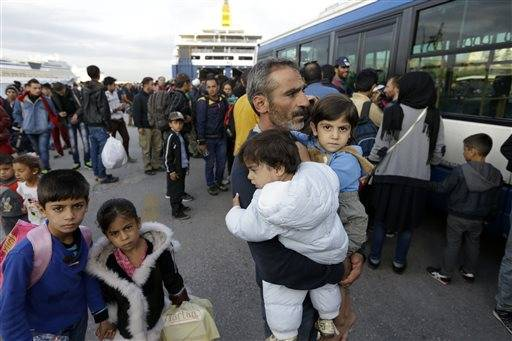 A Syrian man holds his two children as the other two family members follow him after their arrival from the Greek island of Lesbos at the Athens' port of Piraeus, Wednesday, Sept. 30, 2015. The International Organization for Migration says a record number of people have crossed the Mediterranean into Europe this year, now topping a half a million as some 388,000 have entered via Greece.
