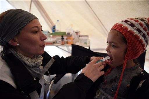 Doctor Barbara Suter from Doctors of the World administers medicine to an Afghan girl at a refugee camp near the northern Greek village of Idomeni, Wednesday, Sept. 30, 2015. The International Organization for Migration says a record number of people have crossed the Mediterranean into Europe this year, now topping a half a million. Some 388,000 have entered via Greece.