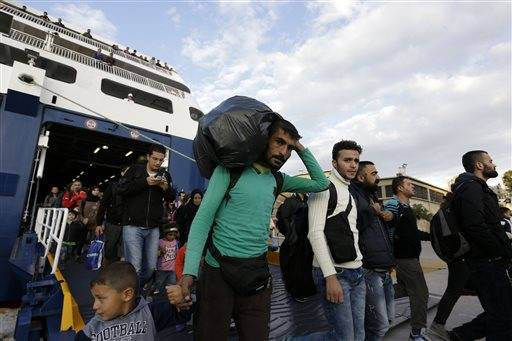 A man carries his belongings as other migrants and refugees arrive on a ferry from the Greek island of Lesbos at the Athens' port of Piraeus, Wednesday, Sept. 30, 2015. The Greek ferry Blue Star Patmos is part of special ferry service for refugees and migrants that carries 1,800 paying passengers. The International Organization for Migration says a record number of people have crossed the Mediterranean into Europe this year, now topping a half a million as some 388,000 have entered via Greece.