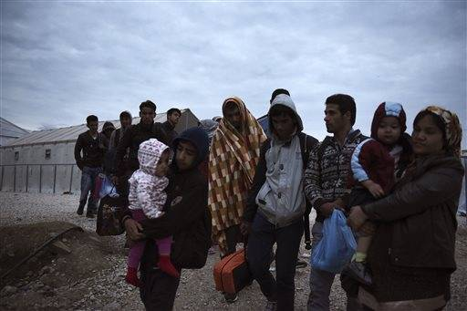 Refugees and migrants walk to cross the border from the northern Greek village of Idomeni to southern Macedonia, Wednesday, Sept. 30, 2015. The International Organization for Migration says a record number of people have crossed the Mediterranean into Europe this year, now topping a half a million. Some 388,000 have entered via Greece.