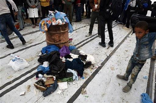 A boy stands near to  a pile of clothes left by migrants, as people wait inside a large tent, to be allowed to cross from the northern Greek village of Idomeni, to southern Macedonia, Wednesday, Sept. 30, 2015. The International Organization for Migration says a record number of people have crossed the Mediterranean into Europe this year, now topping a half a million. Some 388,000 have entered via Greece.