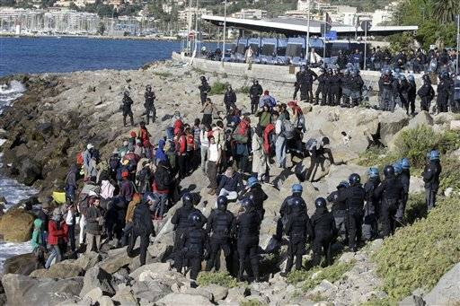 Refugees and migrants are surrounded by Italian police officers in riot gear at the Franco-Italian border in Ventimiglia, Italy, Wednesday, Sept. 30, 2015. Italian police have emptied out a migrant tent camp in the border city of Ventimiglia, prompting dozens of migrants to flee to rocks along the shoreline.