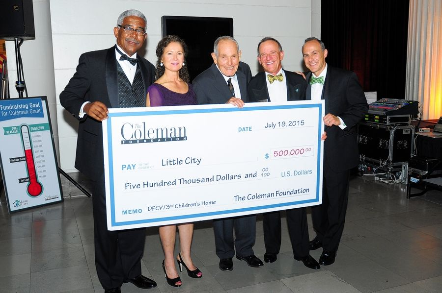 Little City Executive Director Shawn Jeffers, Coleman Foundation Program Officer Rosa Berardi, donor Verne Carson, Little City Chief Philanthropy Officer Ed Hockfield and board Chair Matt Schubert stand with a poster representing the $500,000 grant that was awarded to Little City by the Coleman Foundation.