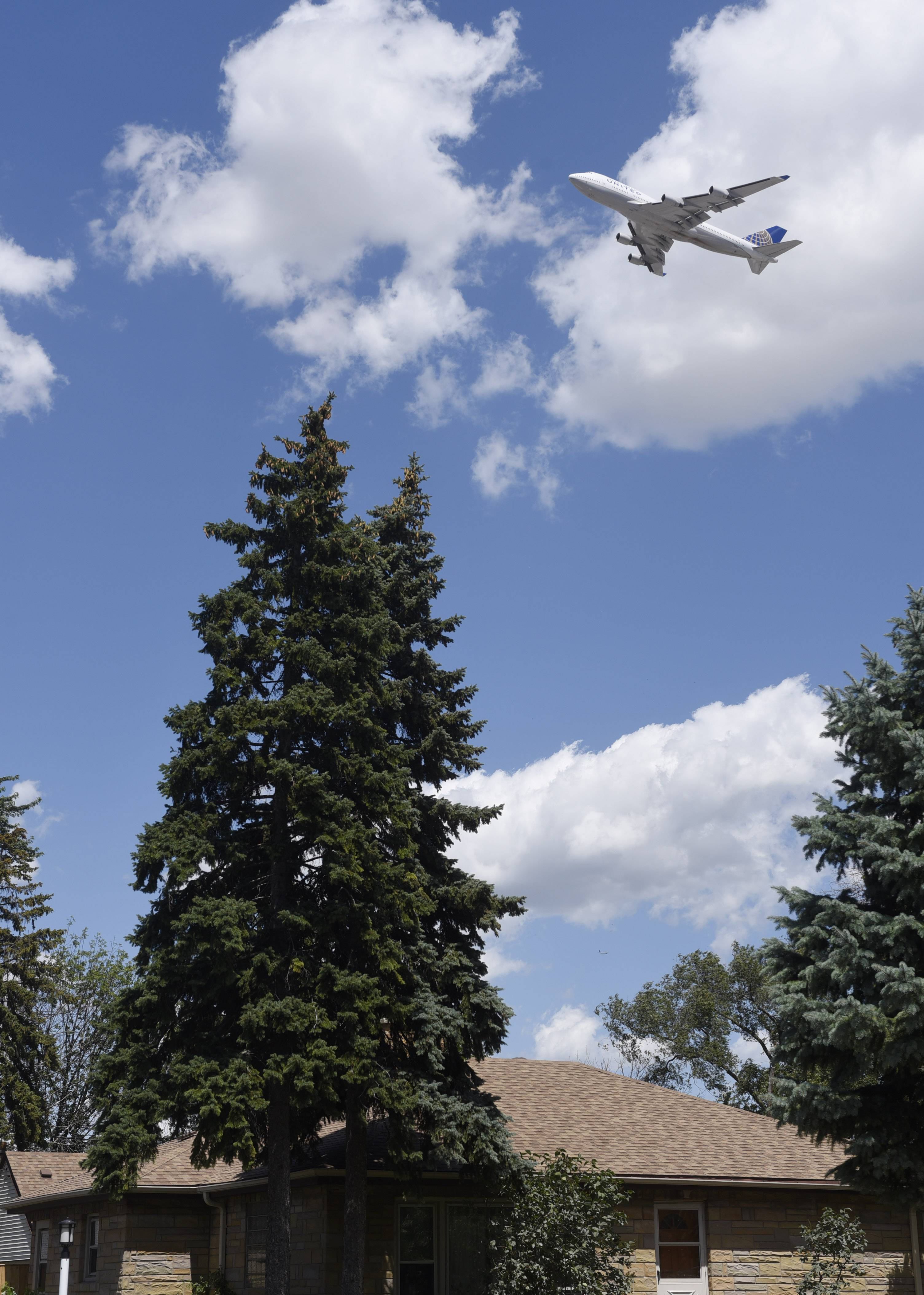 A plane flies above a neighborhood along Hillside Drive in Bensenville after takeoff from O'Hare airport. Homeowners are suing Chicago over jet noise.