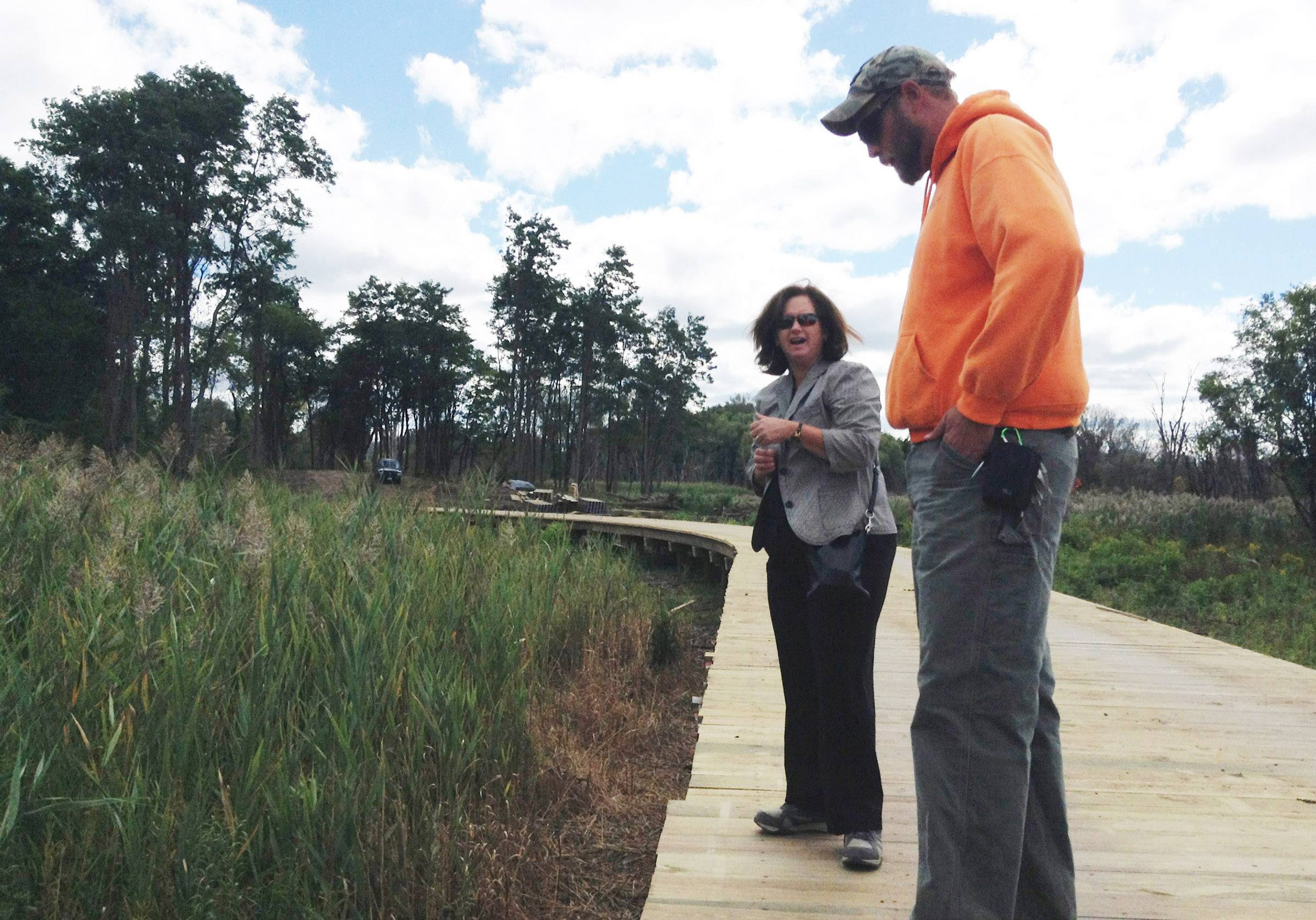 Libertyville Township Supervisor Kathleen O'Connor and Damon Cederberg, township open space field coordinator, look over a section of the 400-foot long boardwalk being built over Bull Creek to connect township properties.