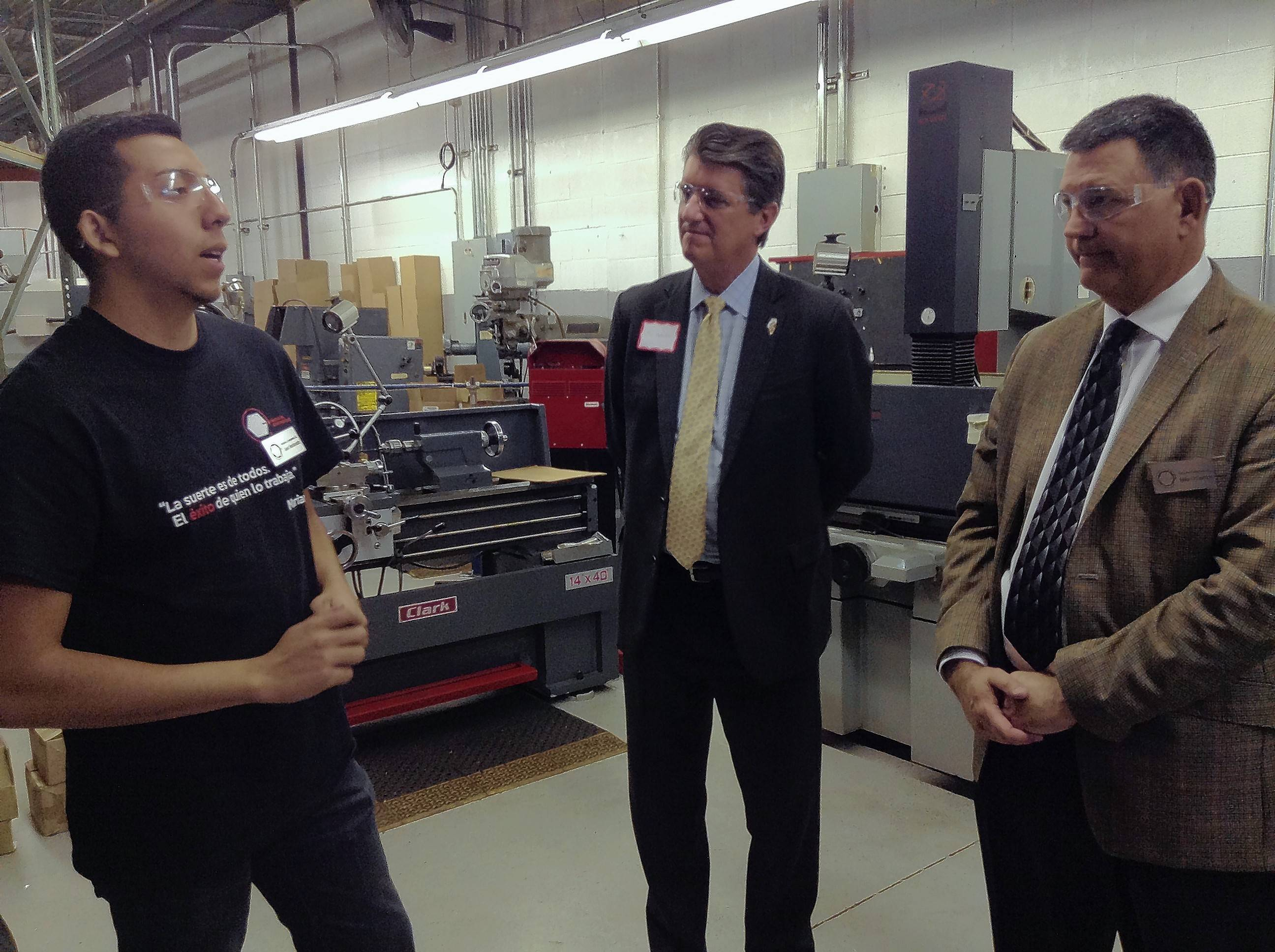 Juan Maldonado, left, an intern at Innovative Components Inc. in Schaumburg and a student at Harper College in Palatine, explains how his education and on-the-job training mesh to Illinois Department of Commerce Director Jim Schultz, center, and Innovative Components President Mike O'Connor, right.