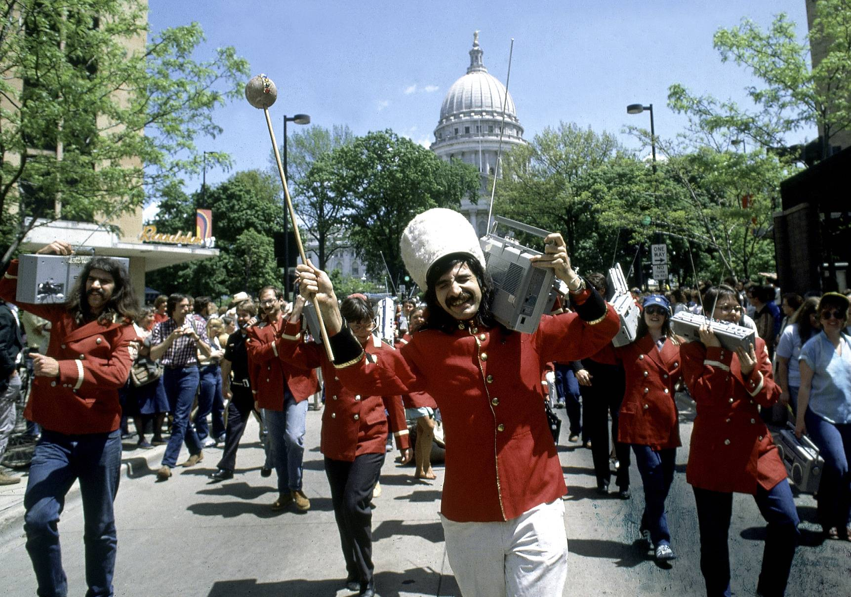 "Leon Varjian leads a boom-box parade down State Street in Madison, Wis. Varjian, who came to the University of Wisconsin-Madison in the 1970s to study in ""the graduate school of fun"" and ended up masterminding such famous pranks as the 1,000 plastic pink flamingoes on Bascom Hill and the Statue of Liberty head on frozen Lake Mendota, has died at age 64, a relative said."