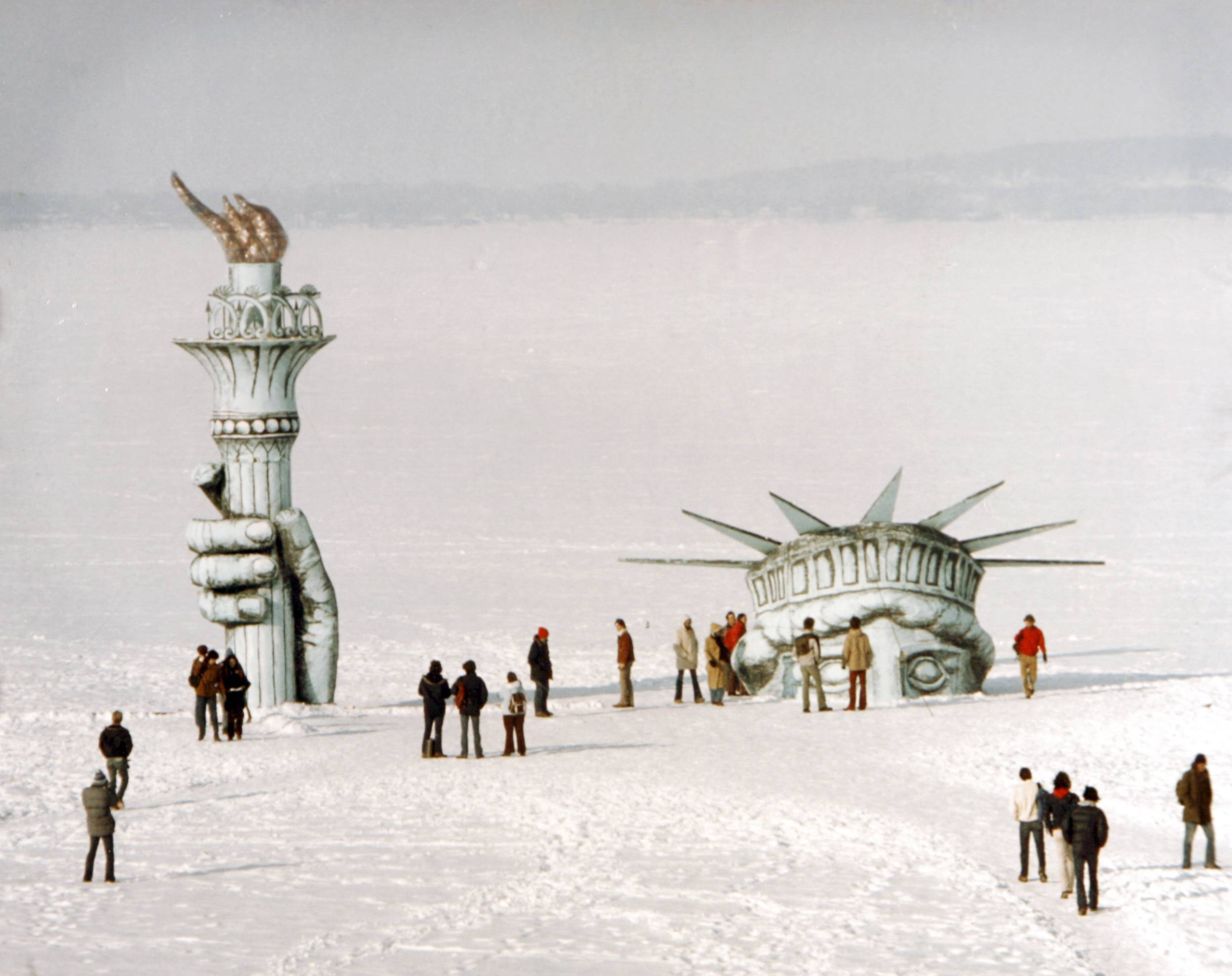 "Madison residents surround ""Miss Liberty"" that appears to be poking through the ice of Lake Mendota behind the Memorial Union in Madison, Wis. The stunt, which garnered national attention, was the handiwork of the whimsical Pail & Shovel Party, headed by Leon Varjian and Jim Mallon. Varjian has died at age 64."